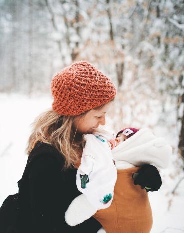 moeder draagt haar kind op een hele koude dag, met sneeuw